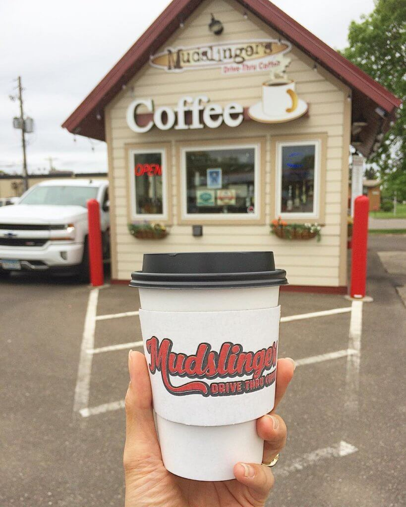 hand holding to-go coffee cup in front of coffee building