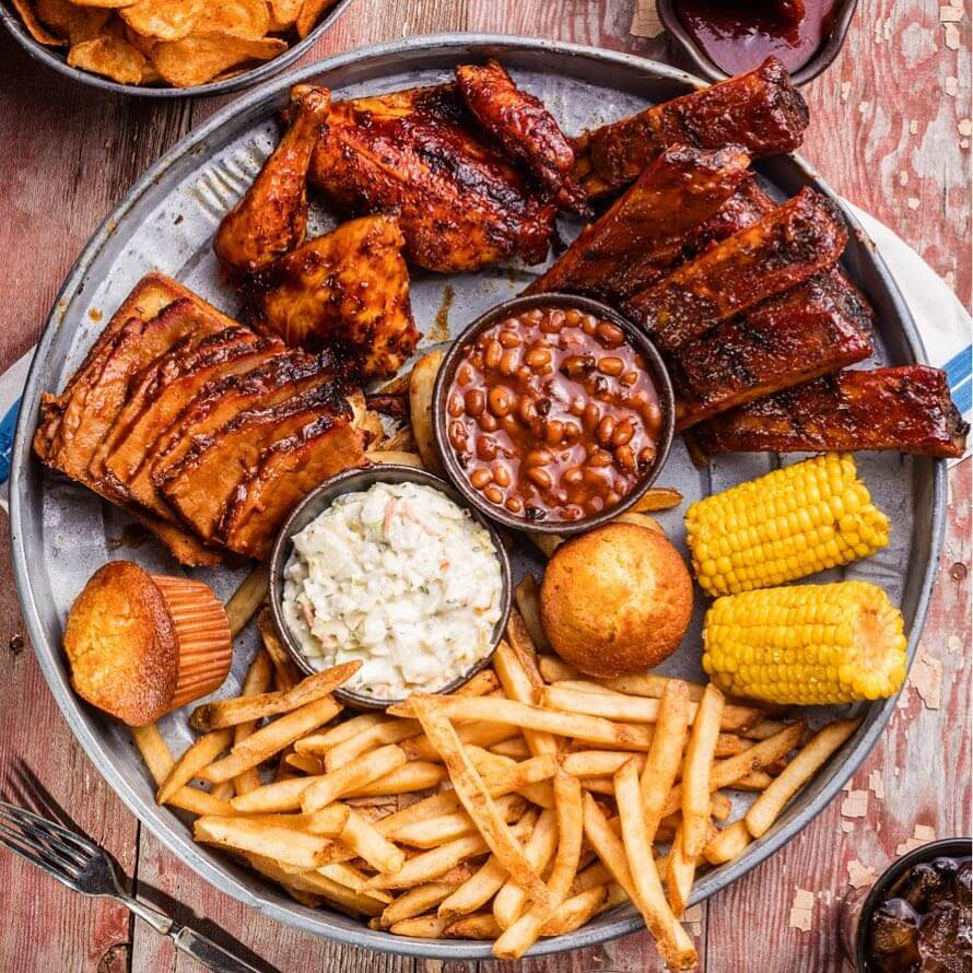 BBQ platter with fries, muffin, corn, and beans