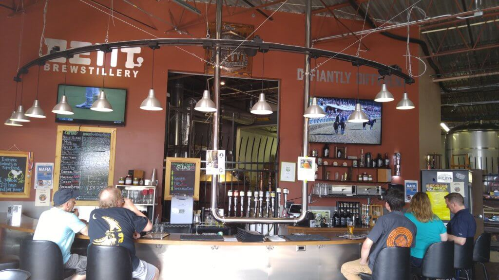 Beer taps and people sitting at counter